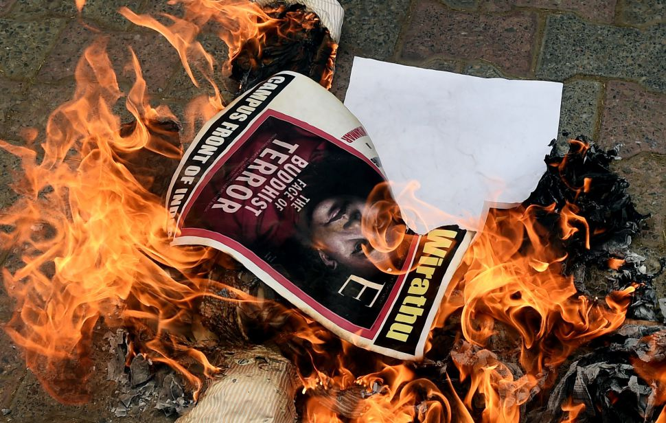 A flyer with Aung San Suu Kyi's face burns in a fire