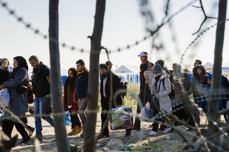 Refugees walk besides barbed wire