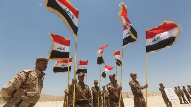 Soldiers hold Iraqi flags