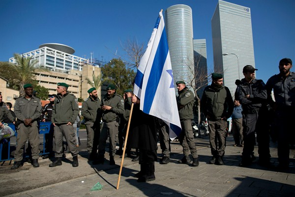 A person holding an Israeli flag